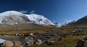冰河谷,沿冰河水永冻土流动的小河,绿色青苔,冰碛冰砾,用永恒报道的高山 库存图片