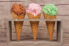 冰淇凌三个奶蛋烘饼锥体在土气持有人的在木头 免版税图库摄影