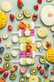 冰淇凌冰棍儿五颜六色的品种用新鲜的切的果子和莓果成份在浅兰的背景,顶视图 免版税库存照片
