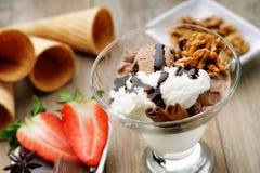 冰淇凌圣代冰淇淋、奶蛋烘饼锥体和切的草莓 图库摄影