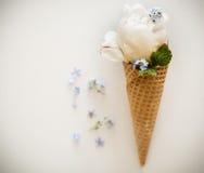 冰淇凌在奶蛋烘饼锥体装饰的薄荷叶和花的immitation 牡丹在与薄荷叶的奶蛋烘饼锥体开花 库存照片