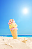 冰淇凌在沙子黏附了在一个晴朗的热带海滩 免版税库存照片