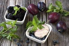 冰淇凌球装饰用在白色板材的莓果 免版税库存照片