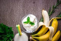 冰淇凌用新鲜的香蕉和薄菏在木桌上 免版税库存照片