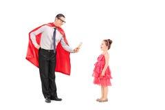 给冰淇凌的超级英雄一个小女孩 免版税库存图片
