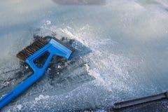 冰清洗汽车,冬天traffi的一块冻挡风玻璃的刮板 库存图片