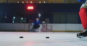 冰球的特写镜头在慢动作的和几个顽童的轻击棒反过来和一个守门员在背景中 股票录像