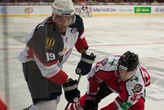 冰球今后从Slovan (布拉索夫)米谢尔Miklik和向前Donbass (顿涅茨克)泰穆Laine 库存照片