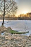 冰由湖岸的被填装的小船 免版税库存照片