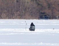 冰的一个人在冬天钓鱼 免版税图库摄影