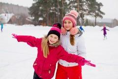 冰的两个可爱的溜冰者女孩 免版税库存图片