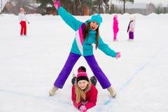 冰的两个可爱的溜冰者女孩 免版税库存照片