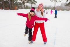 冰的两个可爱的溜冰者女孩 库存图片