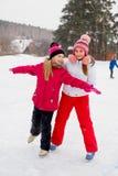 冰的两个可爱的溜冰者女孩 库存照片