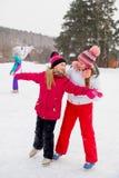 冰的两个可爱的溜冰者女孩 图库摄影