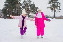 冰的两个年轻溜冰者女孩 免版税库存图片
