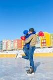 滑冰的夫妇拥抱气球以心脏的形式 图库摄影