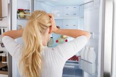 冰箱里面查找的妇女 库存图片