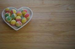 冰糖甜点食物摄影调味用在桃红色黄色和绿色的玫瑰色苹果在一个白色爱心脏盘 免版税库存照片