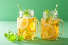 冰茶用柠檬和蜜蜂花在金属螺盖玻璃瓶 图库摄影