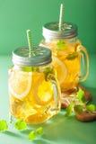 冰茶用柠檬和蜜蜂花在金属螺盖玻璃瓶 免版税库存图片