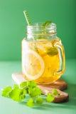 冰茶用柠檬和蜜蜂花在金属螺盖玻璃瓶 库存图片