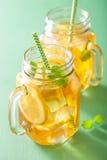 冰茶用柠檬和蜜蜂花在金属螺盖玻璃瓶 免版税库存照片