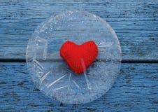 冰锋利的寒冷围拢的温暖的红色心脏谎言在bl的 免版税库存图片