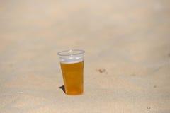 冰镇啤酒照片在热的沙子的 凝析油下落玻璃水 Thi 免版税库存图片