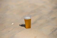 冰镇啤酒照片在热的沙子的 凝析油下落玻璃水 Thi 库存照片