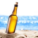 冰镇啤酒botle照片在沙子的 库存图片
