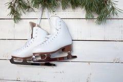 冰鞋和杉木分支在白色木头 库存照片