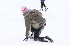 冰鞋的女孩在滑冰场的一个秋天以后起来 免版税库存图片