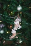 以冰鞋的形式,在云杉的分支垂悬的圣诞节戏弄 库存照片