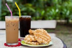 冰冻咖啡和americano用米薄脆饼干(Khao Tan) 免版税库存照片
