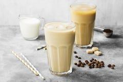 冰冻咖啡用在一块高玻璃的牛奶在灰色背景 库存照片