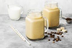 冰冻咖啡用在一块高玻璃的牛奶在灰色背景 库存图片