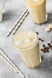 冰冻咖啡用在一块高玻璃的牛奶在灰色背景 免版税库存图片