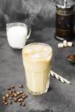 冰冻咖啡用在一块高玻璃的牛奶在黑暗的背景 免版税库存图片