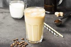 冰冻咖啡用在一块高玻璃的牛奶在黑暗的背景 库存照片