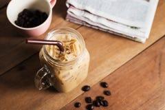 冰冻咖啡用牛奶和报纸在桌上 免版税库存照片