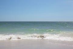 冲上岸在沙滩的绿松石海洋和泡沫似的波浪 免版税库存图片