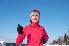 冲刺在冬天培训期间的连续运动员妇女外面在冷雪天气 关闭显示速度和移动 库存图片