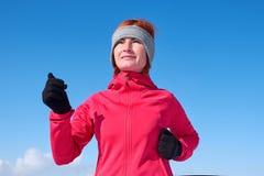 冲刺在冬天培训期间的连续运动员妇女外面在冷雪天气 关闭显示速度和移动 免版税图库摄影