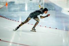冲刺的男性速度溜冰者在滑冰场 免版税库存图片