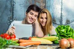 冲浪万维网的年轻夫妇在厨房里 库存照片