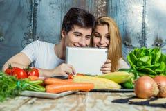 冲浪万维网的年轻夫妇在厨房里 免版税库存照片
