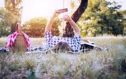 冲浪与智能手机的深色的女孩本质上 免版税图库摄影
