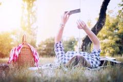 冲浪与智能手机的深色的女孩本质上 图库摄影