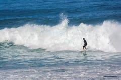 冲浪与碰撞的波浪的人在他后 库存照片